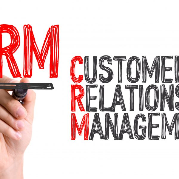 Hand with marker writing: CRM