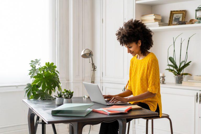 Woman sitting at desk, working, using laptop